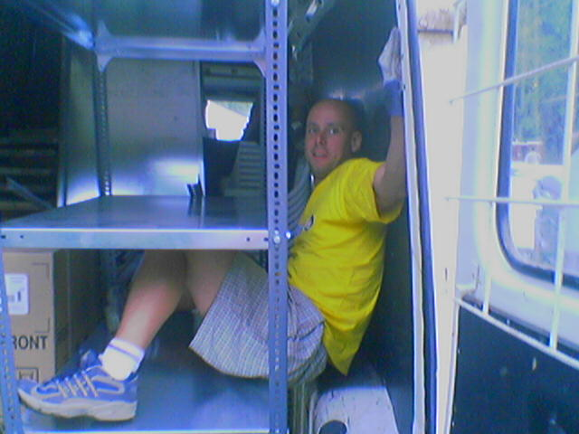 Sziget Festival 'Backstage-boy' stuck between furniture in a van. Funny picture about working at the largest festival in Europe.